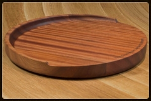 "Idea #1: The Trencher Sapele Mahogany Round Wood Reversible Cutting Board. Beyond stunning and so very thoughtful!  The details: The Grothouse Round Trencher Cutting Board -- 15"" in diameter and 2"" in height -- is a uniquely crafted working surface. The gradual sloped design collects juices in the well at the back of the board — and away from the work area — making it a popular choice for slicing anything from watermelon to carving meat. The trencher reverses to a flat surface, perfect for general chopping and prepping tasks or slicing bread or serving hors d'oeuvres. Shown here in Sapele Mahogany, in red and brown tones with iridescent stripes, this item is just $345 with free shipping! (Other woods are available; optional laser engraving at an additional cost.)"
