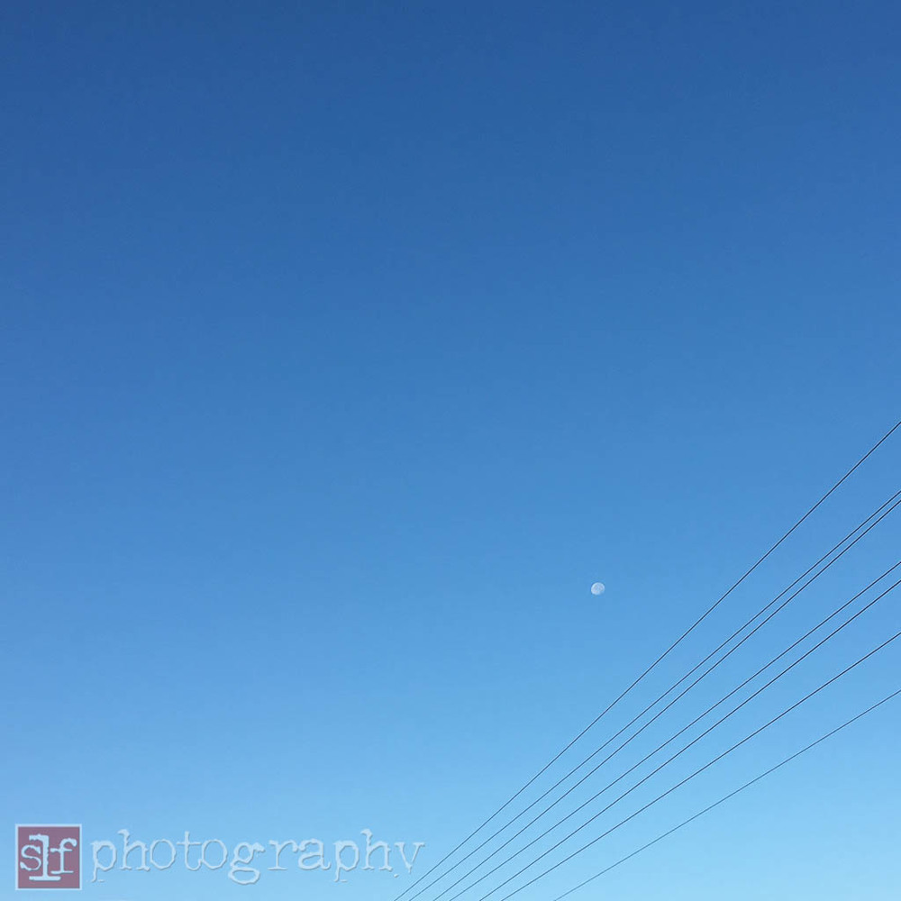 moon is visible about the wires