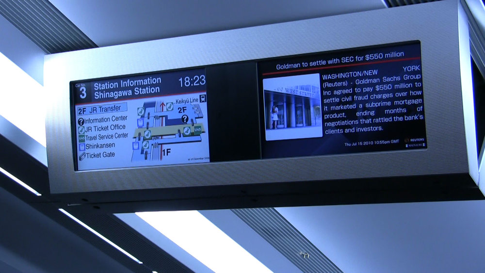 The TVs in the Narita Express showing a map of Shinagawa Station and the news.