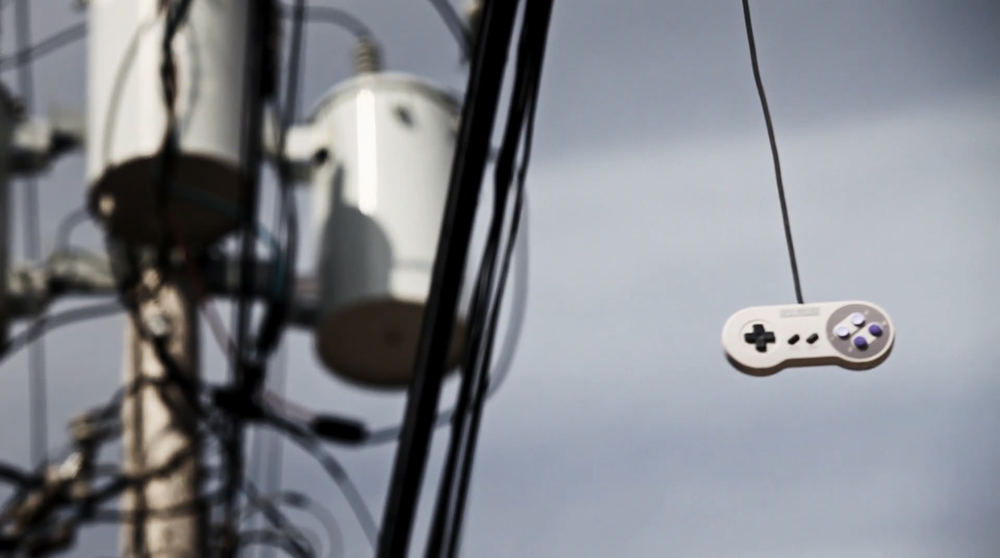A shot from Indie Game: The Movie of an SNES controller hanging from a power line.