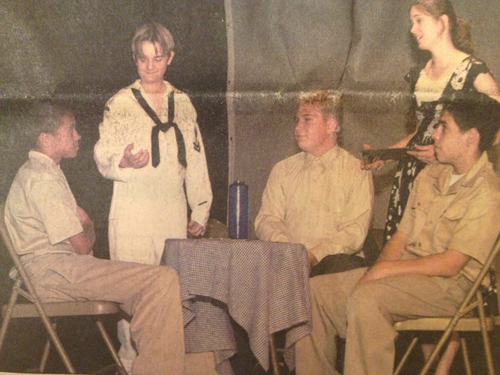 A scan from the front page of my local newspaper for Kilroy Was Here. I'm the sailor pretending to eat a donut for rehearsal.