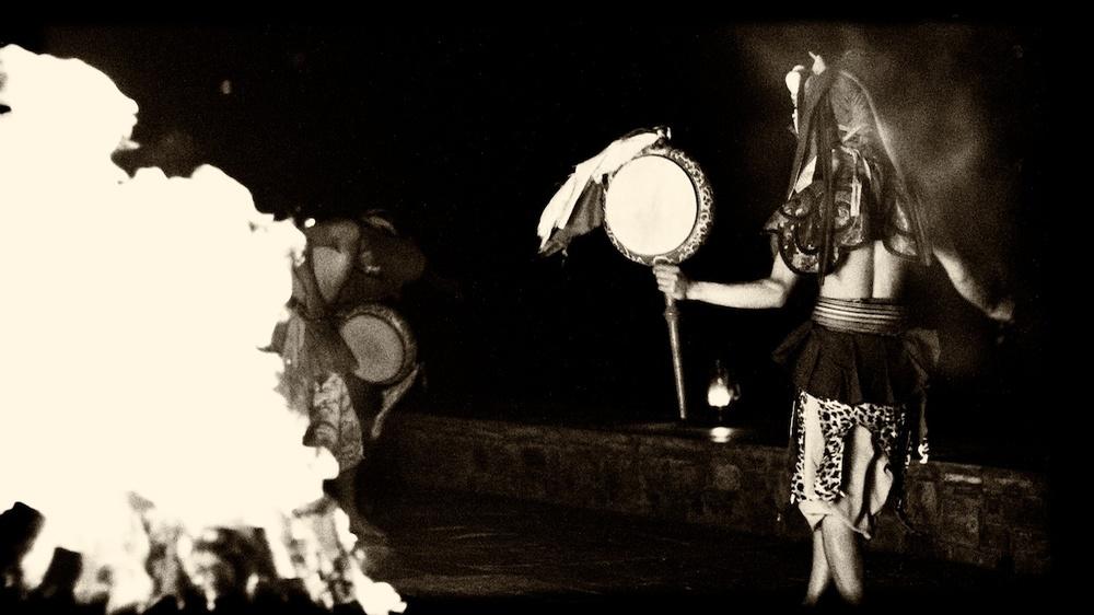 Teschu dancers around a fire pit.