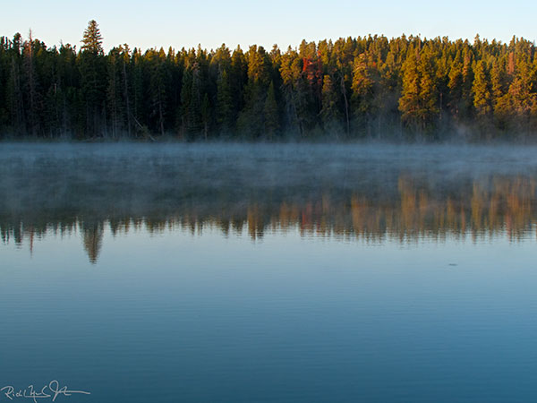 Mists rise of the warm waters of a pond as the sun strikes the treeline.