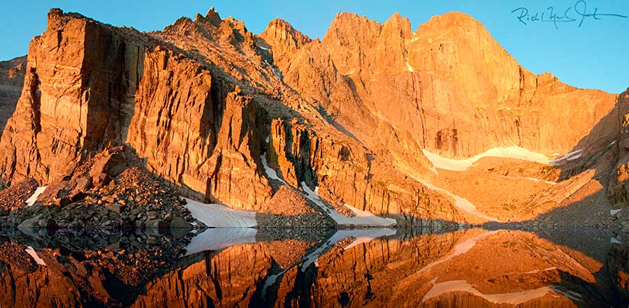 "5:15 AM: The rising sun hits ""The Diamond"" - the east face of Longs Peak - in the distance at right, reflected in Chasm Lake."