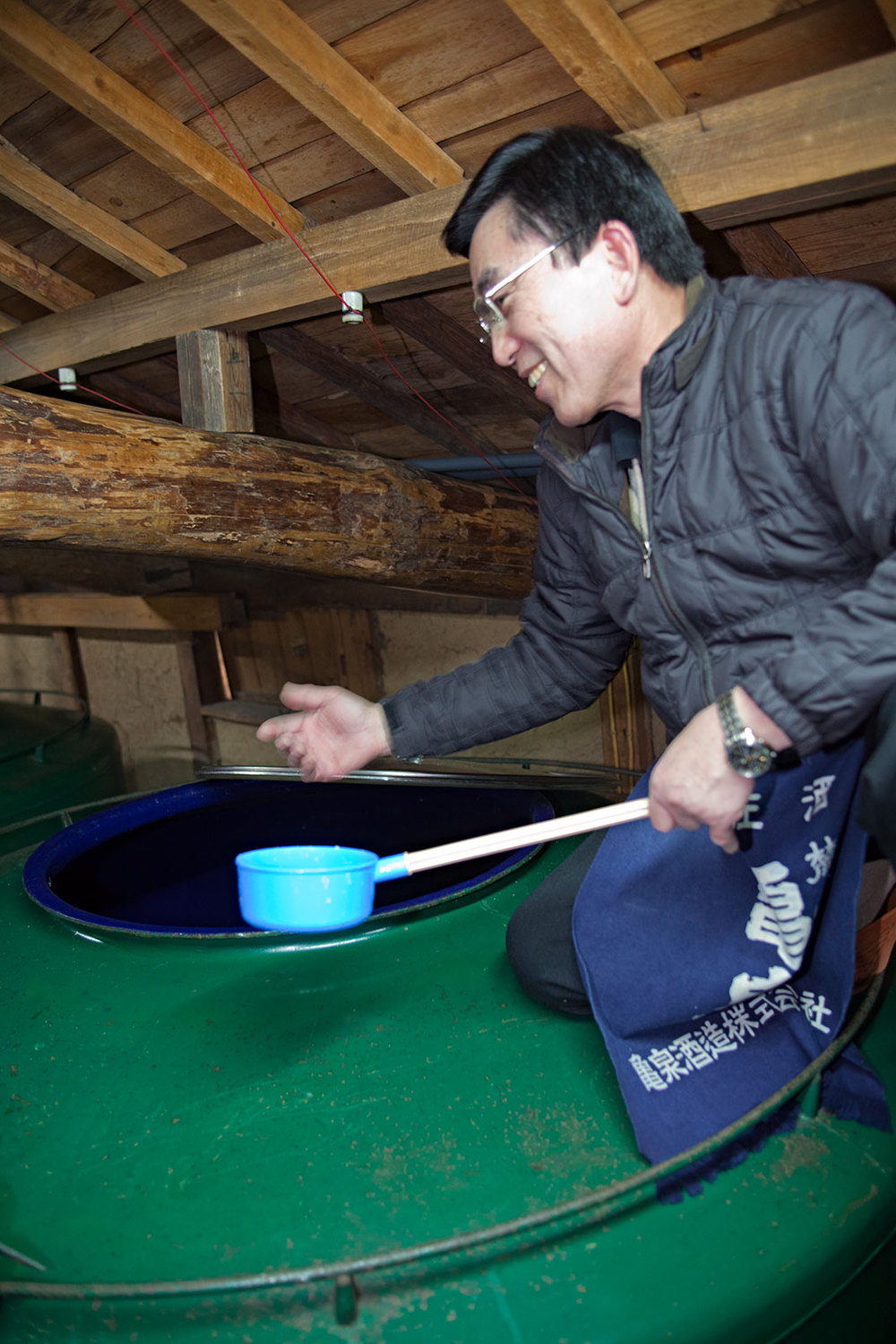 """The """"toji"""" or brewmaster of Kame Izumi, Saibara-san, wafts some air from one of the brewing vats."""