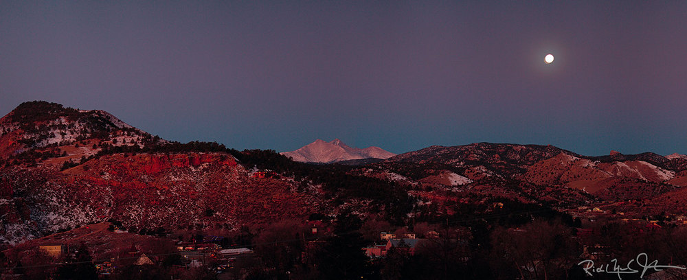 The full moon sets over the Rockies near snow-capped Mount Meeker and Long's Peak, Colorado.