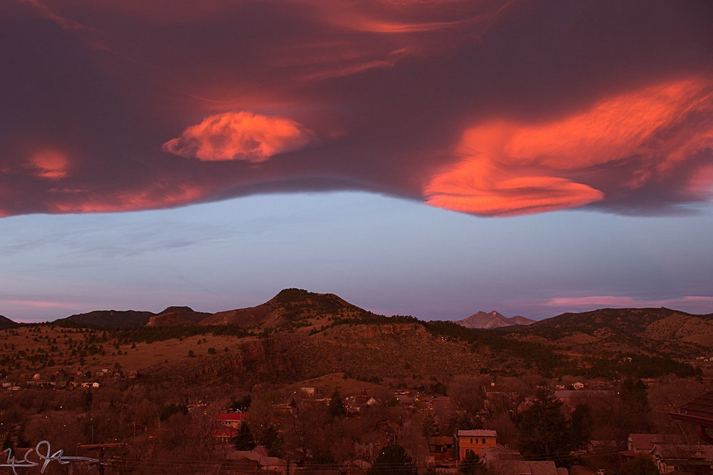 A cloud bank lies just east of the Continental Divide, with some lenticular shapes protruding.