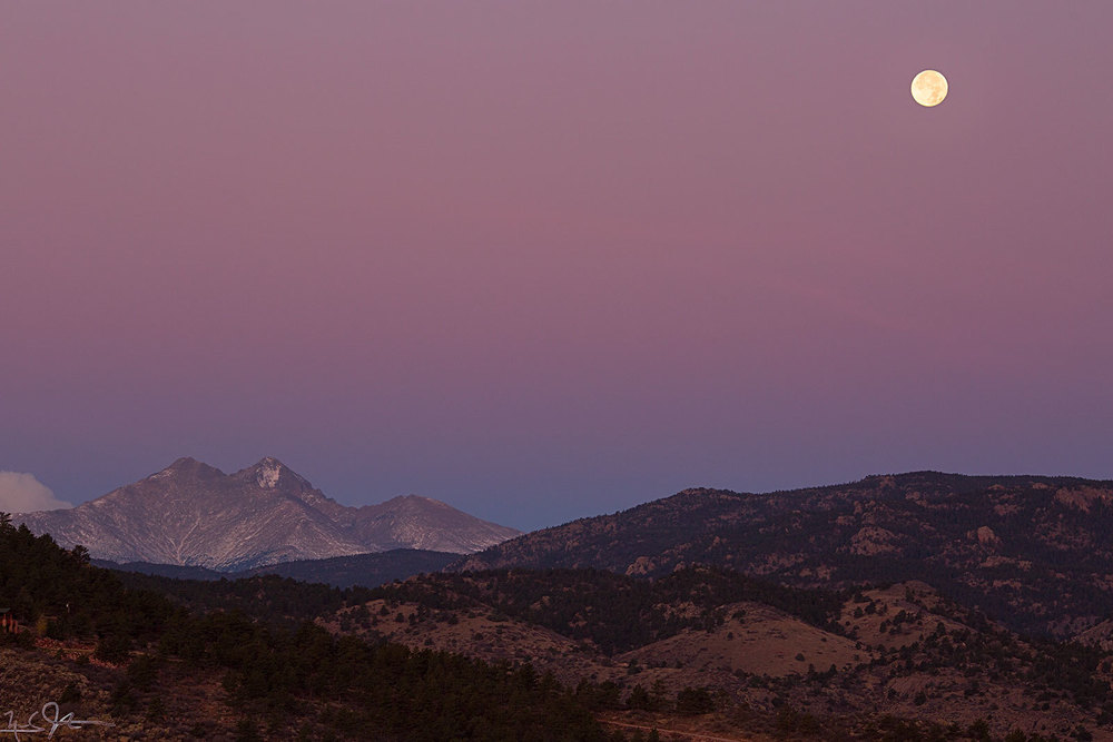 Purple alpenglow suffuses the horizon as the full moon sets just at sunrise.