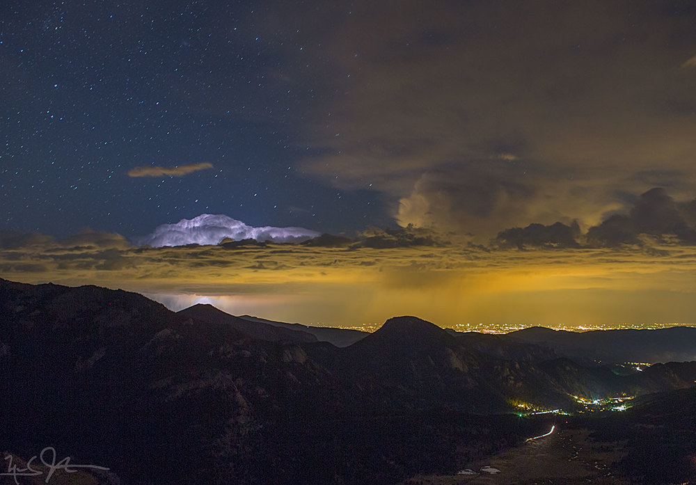 Distant clouds are lit by a lightning bolt.