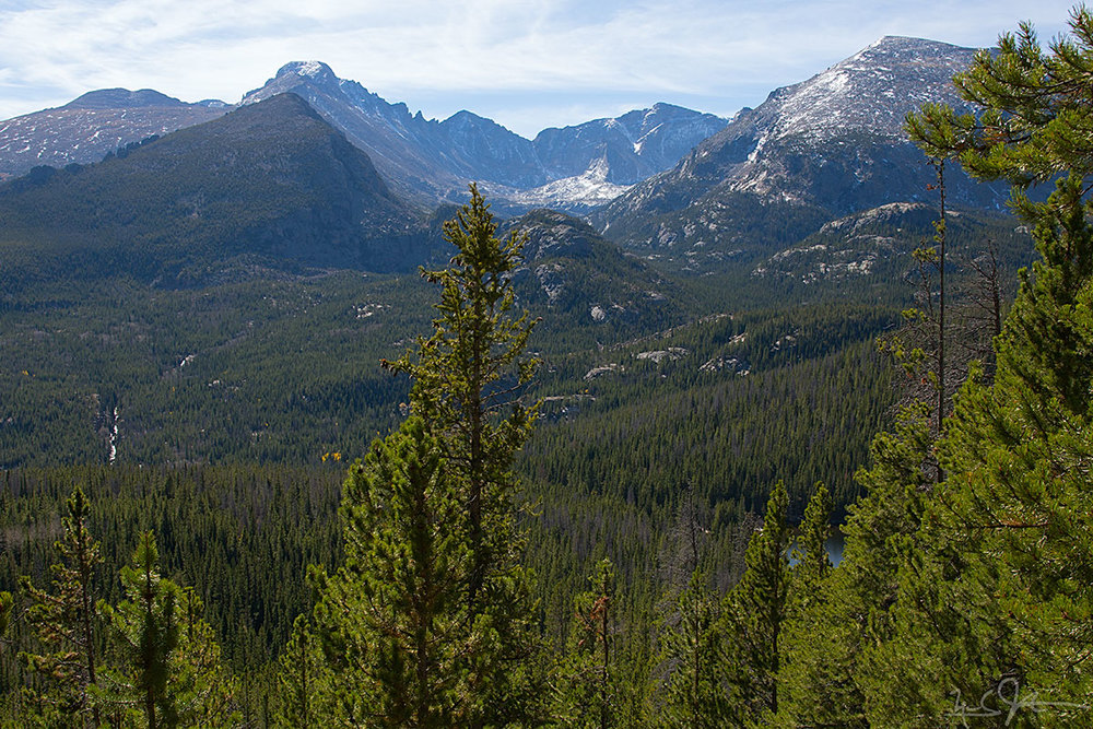 Coming back down the trail, a view southward towards Glacier Gorge, with the Glacier Knobs in the mid-ground and Long's Peak, Keyboard of the Winds, Pagoda Mountain, and Chiefs Head Peak on the horizon. The east end of Bear Lake is visible in the foreground at right.