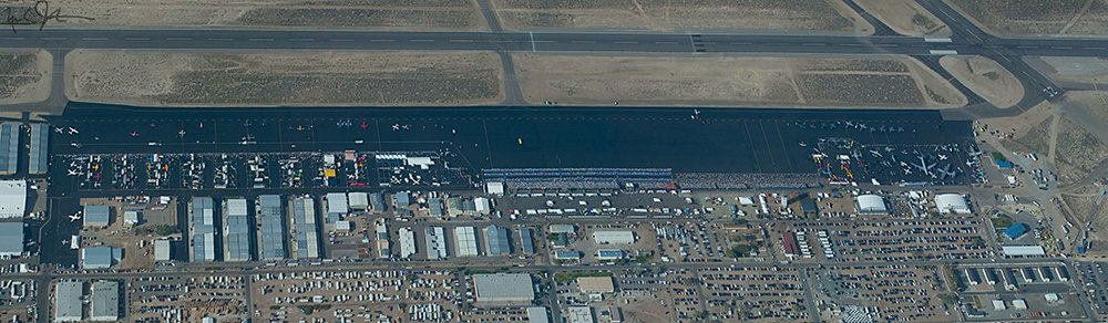 "A view of the ramp from above, looking north, at the Reno Air Races during the event.  Race participant aircraft parking [""the pits""] are at left, grandstands at center, and military aircraft parking at right, with the main runway 8/26 at the top of the photo."