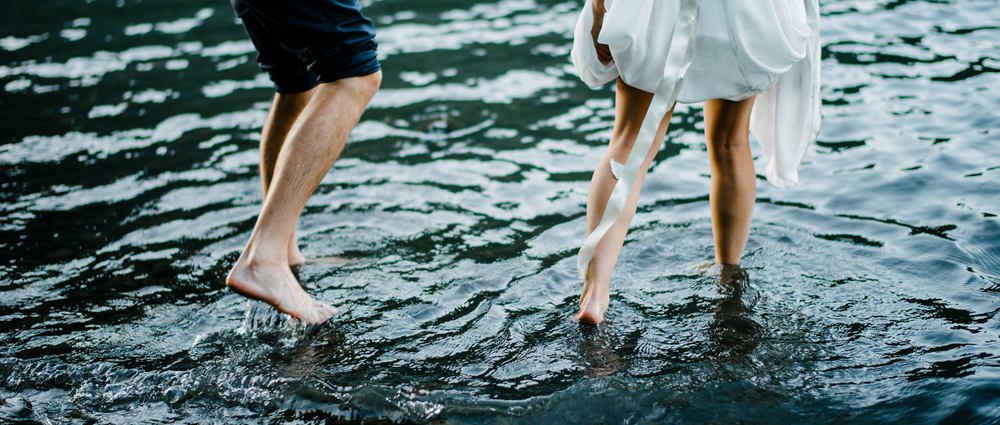 092-bride-and-groom-walking-through-water-at-lake-crescent.jpg