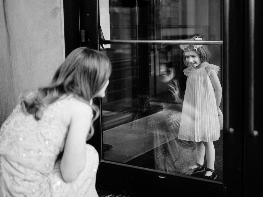 213-documentary-wedding-photo-in-seattle-with-bride-seeing-flower-girl-through-window.jpg
