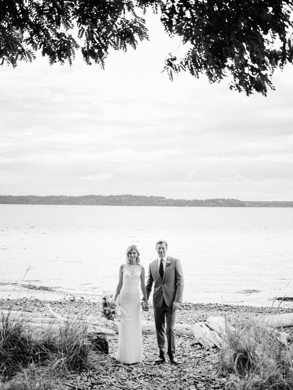 184-wedding-couple-walking-on-driftwood-holding-flowers-by-floret-floral.jpg