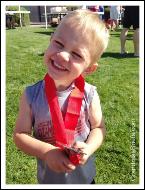 toddler with running medal