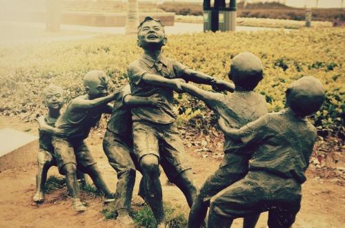 kids playing outside statue