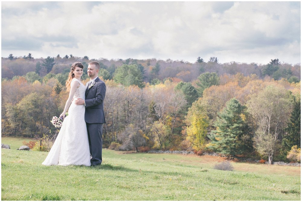A bride and groom stand in front of a background of fall foliage, a aall wedding at the Salem Cross Inn in West Brookfield, MA - Wedding Photography by Ryan Richardson Photography.