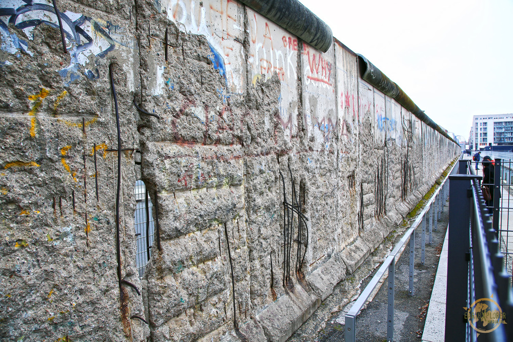 The Berlin Wall was a barrier constructed by the German Democratic Republic starting on August 13,  1961, that completely cut off West Berlin from surrounding East Germany and from East Berlin.