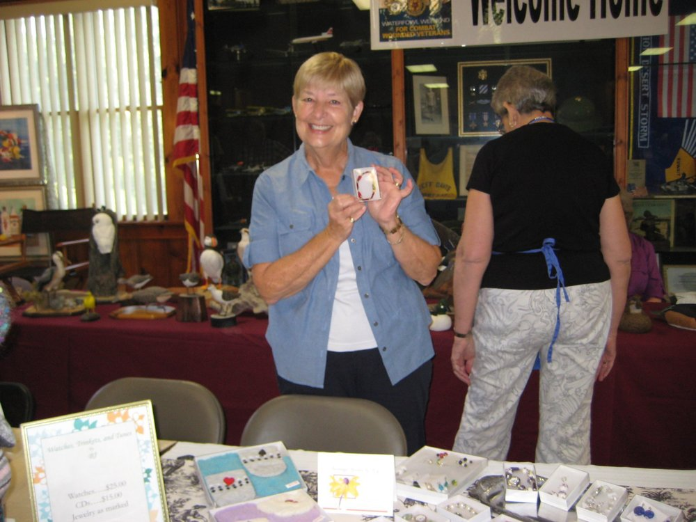 Eleanor Strietman shows off a handcrafted bejeweled watch sent by former-resident BJ McClaeb to exhibit at the Fair along with BJ's CDs.
