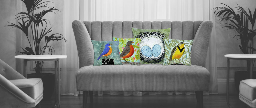 Black and white room view of a sofa with Blenda's artsy bird and nest throw pillows in color
