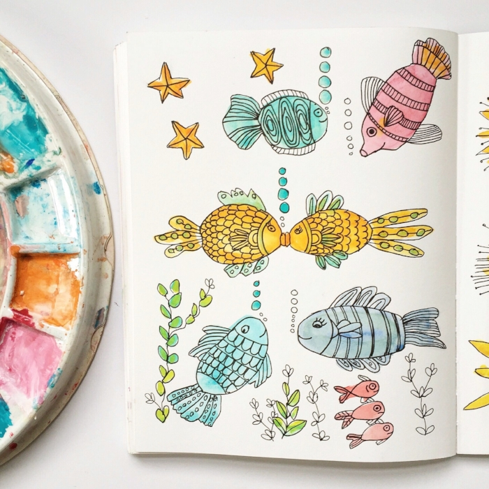 Cute fish watercolor drawings in sketchbook.