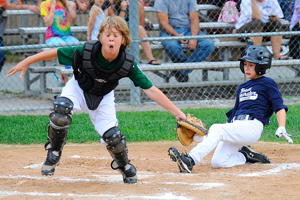 North Leominster's Reid Losey slides safely into home as Westminster catcher Brenden McGuirk tries to handle the throw.