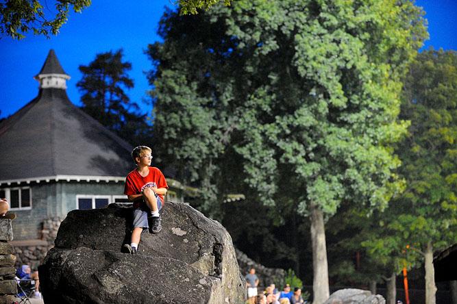 A boy watches a baseball game atop a boulder at Tivnan Field in Worcester.