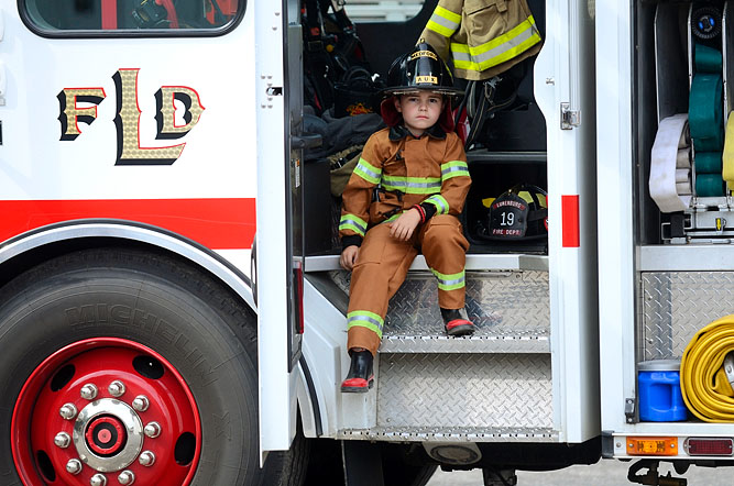 Connor McCormack, son of Lunenburg firefighter T.J. McCormack, sits in a Lunenburg firetruck during an open house at the Lunenburg Department of Public Works.