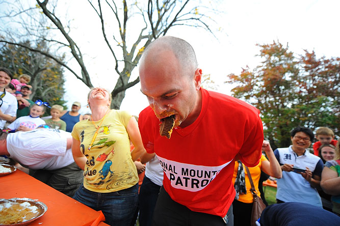 Jessica Johnson of Ashby reacts as Alfred Gadway of Acton takes a large bite of pie crust while participating in the pumpkin pie-eating contest, which he came in a close 2nd, during the 22nd Annual Pumpkin Festival on the Ashby Town Common.