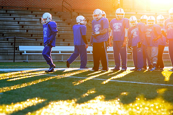 The Leominster High School varsity football team line up for a drill during an evening practice.
