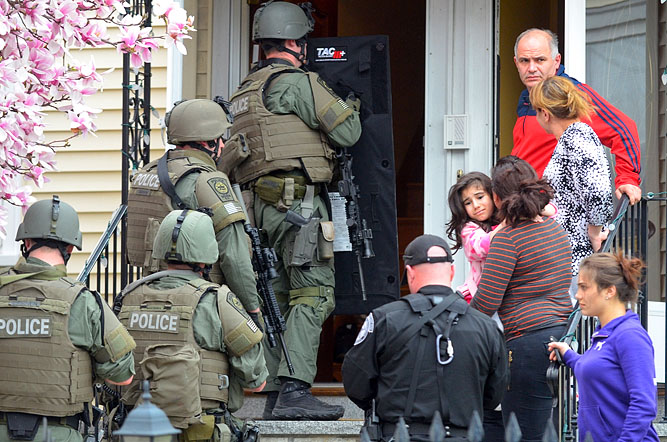 Residents stand outside as NEMLEC SWAT officers enter the home during a door-to-door search throughout a Watertown neighborhood.