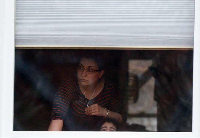 A woman and a small child look out their window as a SWAT team moves in to search their home.