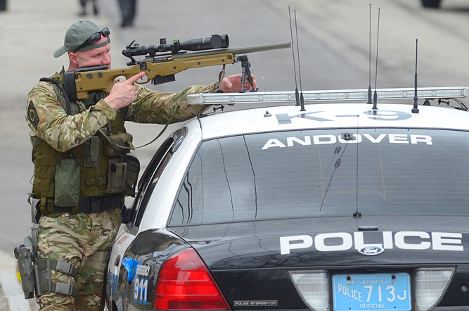 A police officer looks through the scope of his sniper rifle as SWAT searches a Watertown apartment.