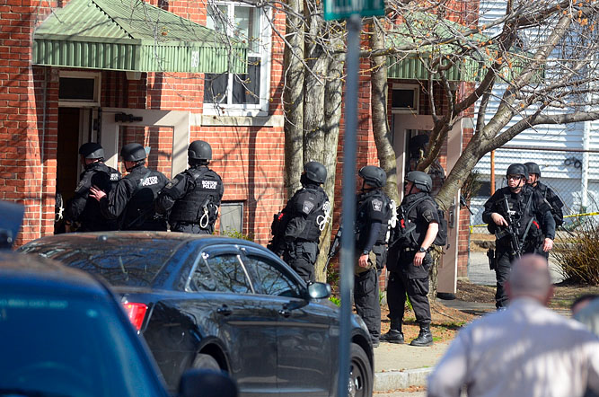 A SWAT team enters a 4-story building during a search.