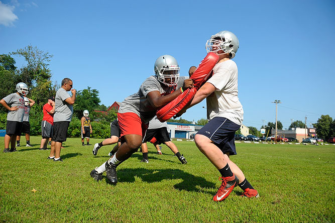 Fitchburg High School senior Raymond Teague, 18, (left) and junior Steven Bartolomeo, 16, participate in a blocking drill during football practice on 8/20/13.