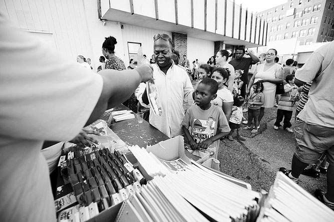 Nana  Bonnah, Jr., 6, of Leominster, with his father Nana Bonnah of  Leominster, gets free school supplies at the 2013 Back to School Rally  at New Creation Community Church on Boulder Dr. in Fitchburg. Also at the  event, free haircuts were given to boys and girls got their nails done.