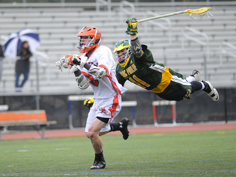 Walpole's Mark Niden attacks as King Philip's Bill Roberts leaps in an attempt to knock the ball away. Niden scored during the play.  Wicked Local Staff Photo / Brett Crawford
