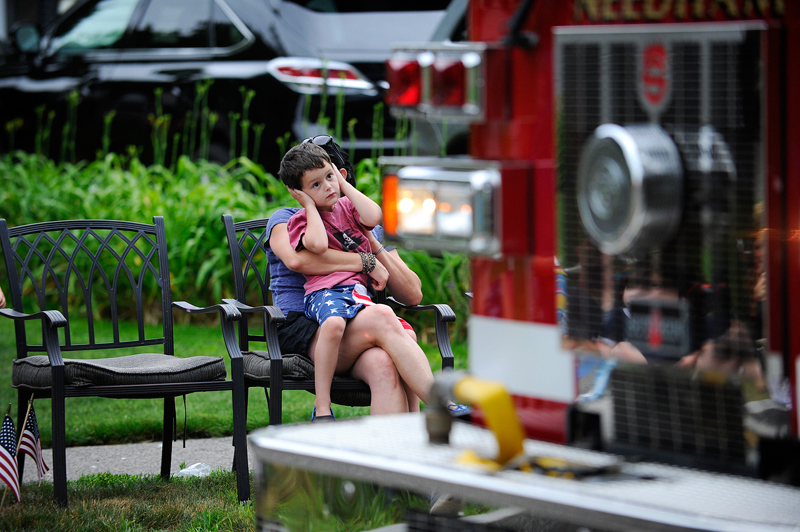 Ashton Glynn, 4, of Shrewsbury covers his ears while seated on his mother Laura Glynn's lap as fire engines sound their sirens as they make their way down Webster St. Wicked Local Staff Photo / Brett Crawford
