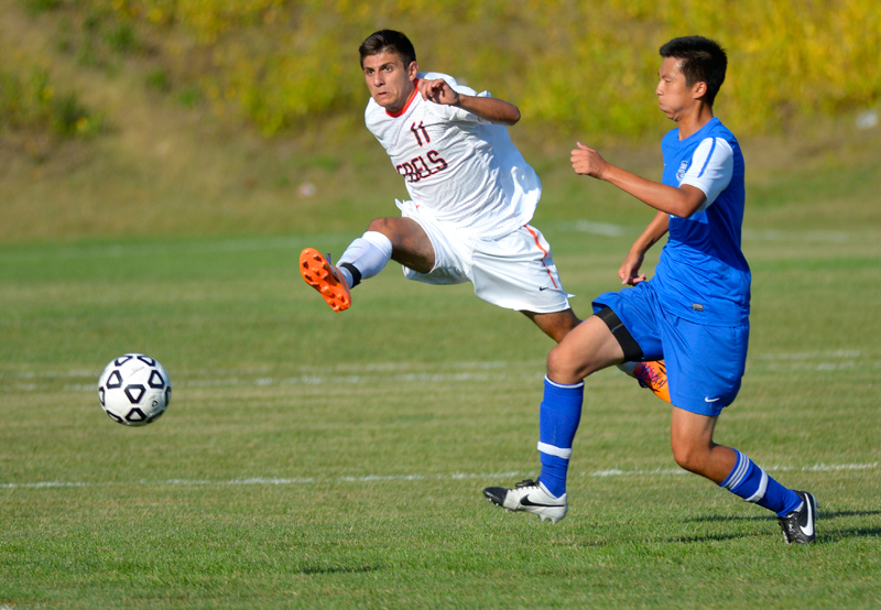 Walpole's Nabil Chamoun takes a shot (#11) while defended by Brookline's JK Suh on September 5, 2014. (Wicked Local Staff Photo / Brett Crawford)