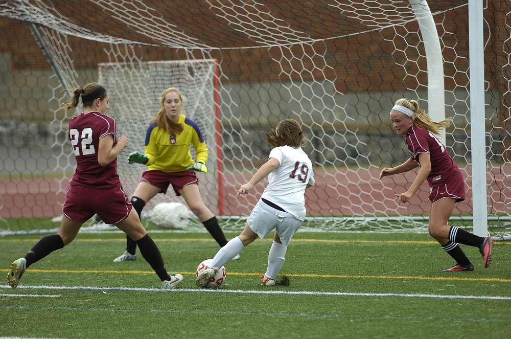 Dedham's Meghan McFarland (19) fires a shot for a goal against Weston goalie Natalie Pettirossi while Weston's Tally Shea (left) and  Kelsey McGeough defend during Monday's game, Oct. 13, 2014. Dedham took the win, 3-1. (Wicked Local Staff Photo / Brett Crawford)