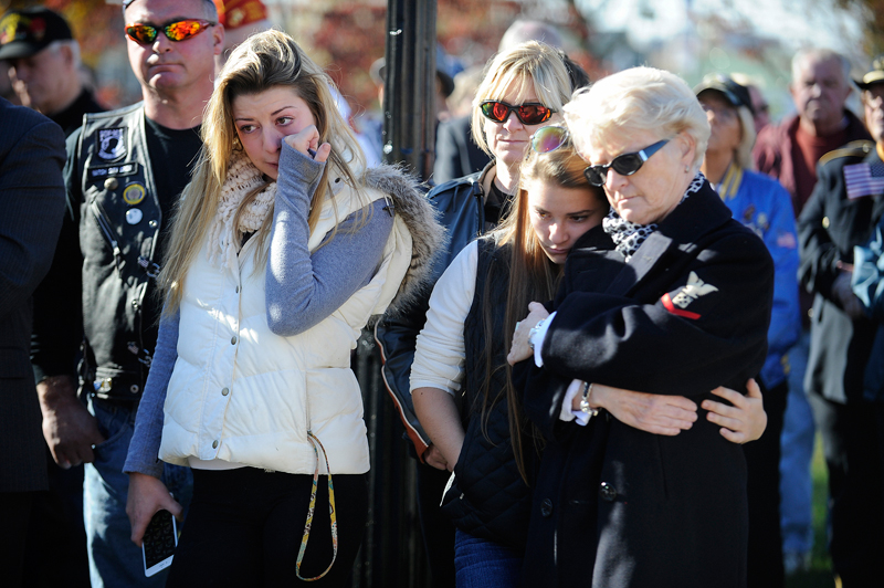 "Sisters Kelley Williams, 19, and Erin Williams, 17, both of Bedford, with their grandmother Nancy Hancock of Waltham, observe the dedication ceremony for ""Wally's Way,"" the walkway from Main St. to the Circle of Remembrance on Waltham Common, named in honor of former Waltham resident and Bronze Star recipient Walter E. Hoyt Jr. on Veterans Day, Tuesday, Nov. 11, 2014. Hancock was a longtime companion to Hoyt Jr. (Wicked Local Staff Photo / Brett Crawford)"