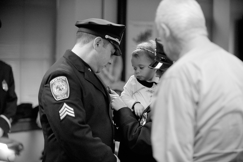 Newton Police Sergeant Jeffrety Boudreau has his badge pinned by his wife Officer Kimberly Boudreau, along with his daughter Deborah, 1 1/2, and grandfather, retired Newton Polcie Detective Captain Walter Drew during Newton Police Department's promotional swearing-in ceremony on Wednesday, Nov. 26, 2014. (Wicked Local Staff Photo / Brett Crawford)