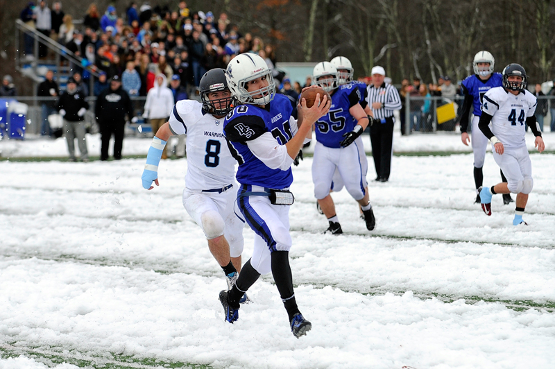 Dover-Sherborn's Brandon Miner runs for extra yards while chased by Medfield's Joseph Davanag during the Thanksgiving Day game in Dover on Thursday, Nov. 27, 2014. (Wicked Local Staff Photo / Brett Crawford)