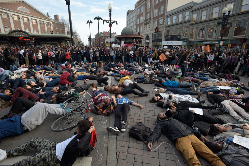 """Protesters, including Harvard and Cambridge Rindge and Latin students, lie down on 2A in Harvard Square in Cambridge during the national """"Hands Up Walk Out"""" protest against police violence on Monday, Dec. 1, 2014. (Wicked Local Staff Photo / Brett Crawford)"""