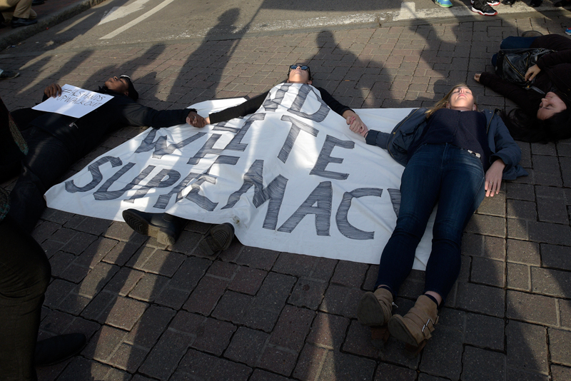 """Protesters start lying down on 2A in Harvard Square in Cambridge during the national """"Hands Up Walk Out"""" protest against police violence on Monday, Dec. 1, 2014. (Wicked Local Staff Photo / Brett Crawford)"""
