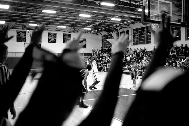 Dedham's Hakeem Animashaun takes a free-throw as Dedham cheerleaders send him positive vibes during a game against Braintree on Friday, Dec. 19, 2014. Braintree won 44-43. (Wicked Local Staff Photo / Brett Crawford)