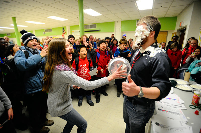 Wellesley Middle School 7th-grader Ariana Furlong reacts after throwing a whipped cream pie at the face of 7th grade english teacher Alex Stanmyer during a fundraiser for the Parkinson's Disease Foundation on Friday, Feb. 6, 2015. (Wicked Local Staff Photo / Brett Crawford)