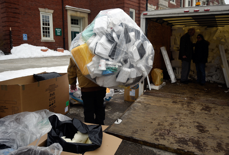 Dave Sherman, owner of RefoamIt, carries a large bag of foam meat trays, cups, and egg cartons to a pile at the 3R Depot, a part of Brookline's 5th annual Climate Week, at the town hall on Saturday, Feb. 7, 2015. Sherman's company processes the styrofoam items and sells them to a company that makes picture frames out of the recycled material.  (Wicked Local Staff Photo / Brett Crawford)