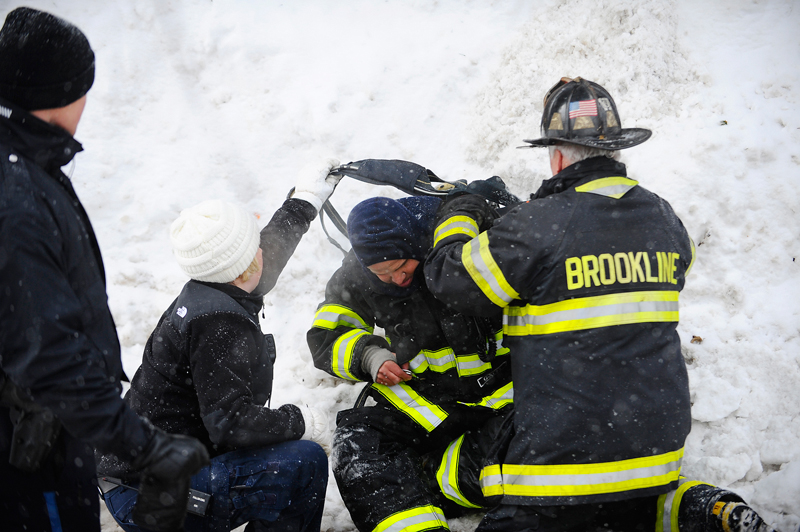A firefighter receives medical attention at the scene of a house fire at 33 Edgehill Rd. in Brookline on Tuesday, Feb. 17, 2015. (Wicked Local Staff Photo / Brett Crawford)