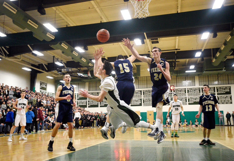 Westwood's Will Jessup puts up a blind shot during a drive to the basket past the defense of Foxborough's Brandon Moy (15) and Dylan Linehan (24) during a Division 2 South quarterfinal game on Friday, Feb. 27, 2015. Foxborough won 59-47. (Wicked Local Staff Photo / Brett Crawford)
